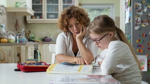 Mother helping daughter with her homework at the table in the dinning room.